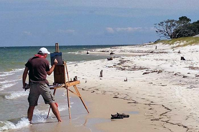 Billy Solitario painting on the beach
