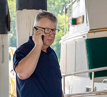 Mark Corke BoatUS Editor using a cellphone next to his boat